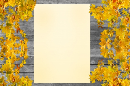 Note paper at wooden background with leaf decoration