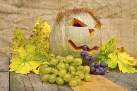 Fallen leaves with pumpkin and grapes,autumn background photo