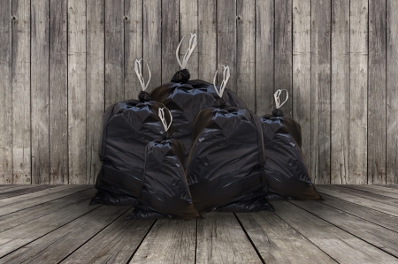 Pile of full black garbage bags with wooden background photo