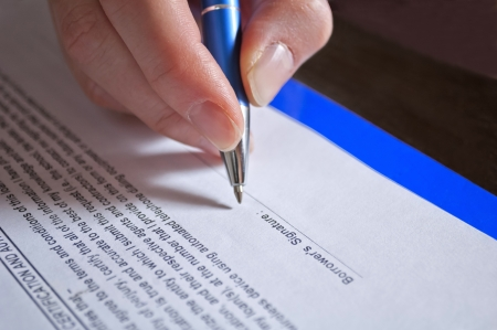 installment: Concept of signing loan agreement with pen in hand