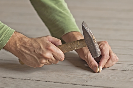 Man hands driving nail with hammer, building works Stock Photo