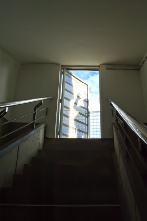 Staircase leading to shadows on door, business metaphor photo