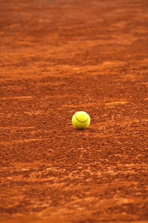 Tennis ball on red clay court Stock Photo
