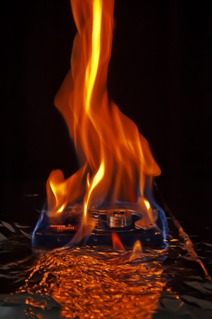 Computer hard disk on fire, burning in flames Stock Photo