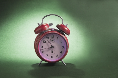 Red old style alarm clock on illuminated background with shadow Stock Photo