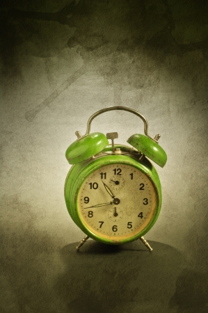 Green old style alarm clock over a grunge background Stock Photo - 17259520
