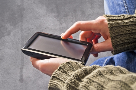 Touchscreen phone in the hands over a grunge background Stock Photo - 17544769
