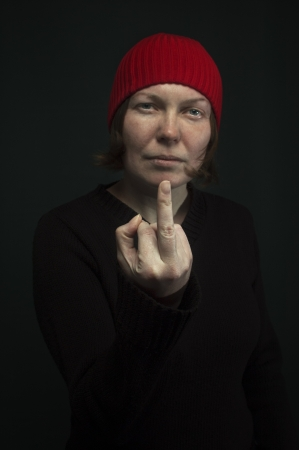Aggressive punk woman with red cap showing middle finger, low key image  Selective focus on middle finger  photo
