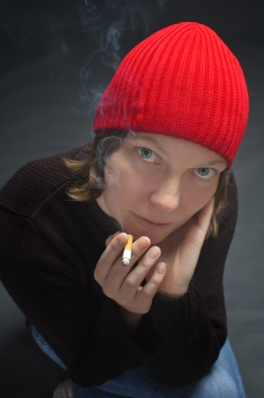 Beautiful woman with red cap smoking cigarette Stock Photo - 17542007