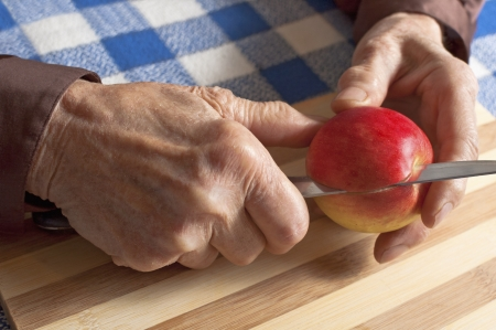 Old woman slicing an apple Stock Photo