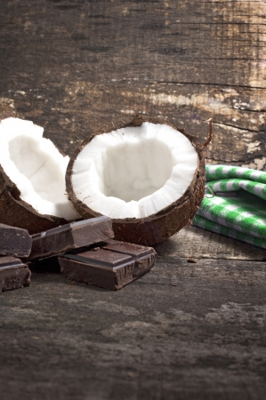 Coconut with chocolate on old wooden background Stock Photo