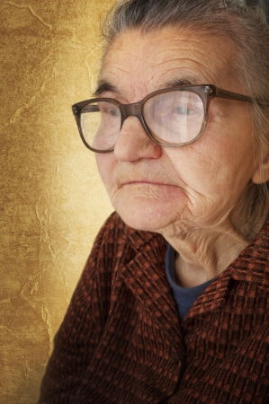 Portrait of an old woman on a vintage background  Dreaming the past photo