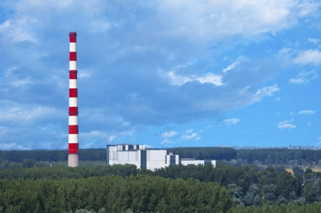 bioenergy: District heating and power plant using bio fuel to produce heat and electricity  The heating plant is surrounded by forest  Stock Photo