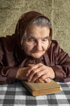 Elderly woman holds bible and pray  Stock Photo