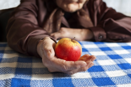 Old woman holding an apple photo
