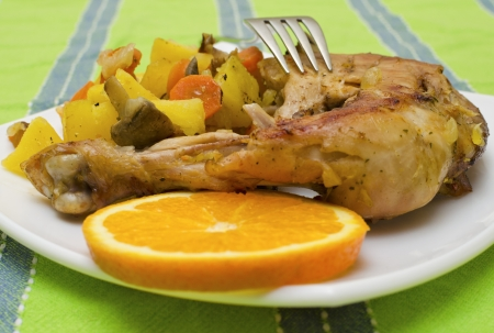 Grilled chicken leg with slice orange and vegetables