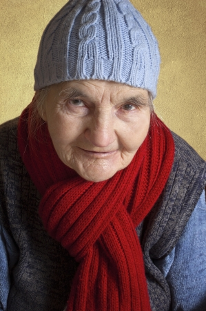 Portrait of a smiling elderly woman with blue cap and red scarf  Stock Photo