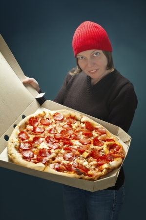 Successful delivery worker woman, showing big pizza ,selective focus on pizza.