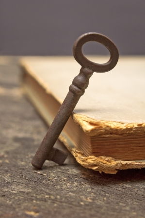 Old rusty key and vintage book on wooden table