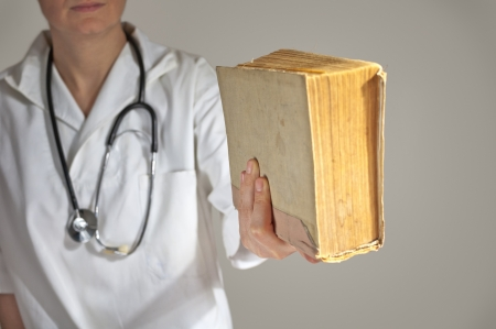 Female medicine student holding a book , close up image with shallow depth of filed with focus on hand with a book
