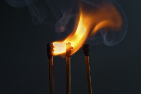 Matchsticks with flame on dark background  Stock Photo
