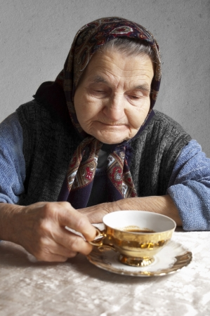 Portrait of an elderly woman drinking coffee on a vintage background  Dreaming the past