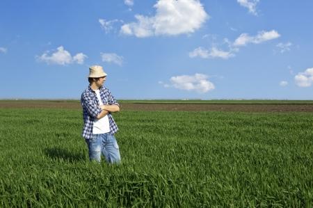 Farmer in a wheat field against blue sky
