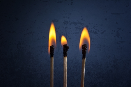 Matchsticks with flame over a dark grunge background photo