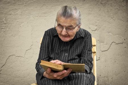Elderly woman sitting in a chair and reading Bible Stock Photo