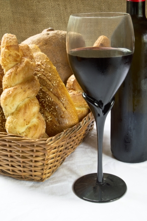 Still life assortment of bread with a glass of red wine and bottle  Selective focus on glass of red wine  photo