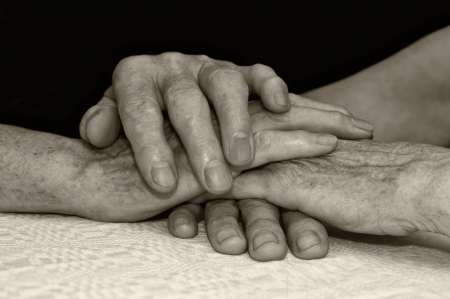Old people hold each others hands. Selective focus with shallow depth of field.