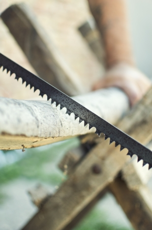 Hand cutting wood with hand saw  Selective focus with shallow depth of field
