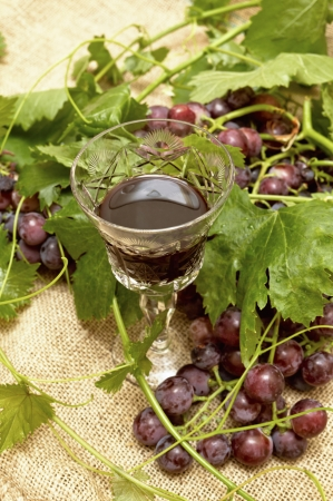 Red wine in wine glass with sweet grapes  Selective focus with shallow depth of field