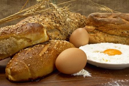 Still life with tasty fresh crunchy bread and raw eggs  Stock Photo