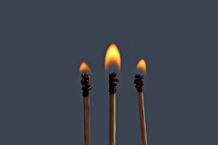 Matchsticks with flame over a dark background  photo