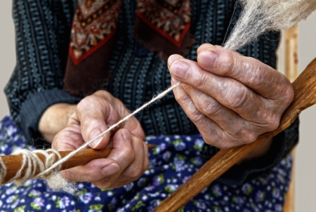 The hands of the elderly woman spinning a wool