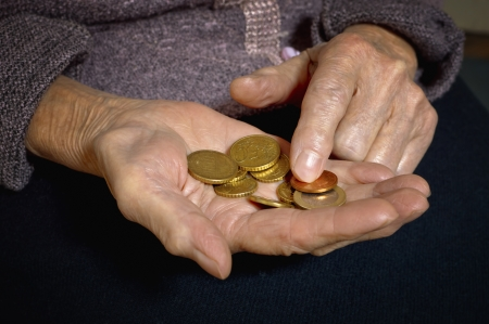 Euro coins in old woman