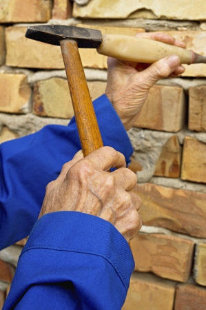 Elderly hand holding a hammer and chisel  Construction background  Stock Photo