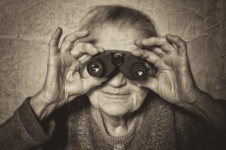 Vintage photo of elderly woman looks through binoculars.
