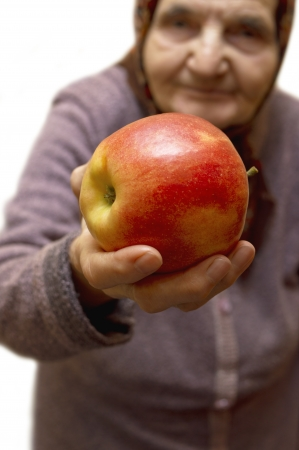 Old woman holding an apple  Selective focus on apple