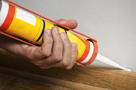 Caulking silicone from cartridge on wooden batten