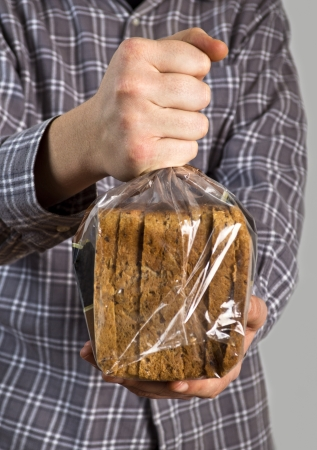 Hand holding sliced brown  rye  bread in the plastic bag