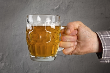 Hand holding fresh light beer making a toast, over a grunge  Stock Photo