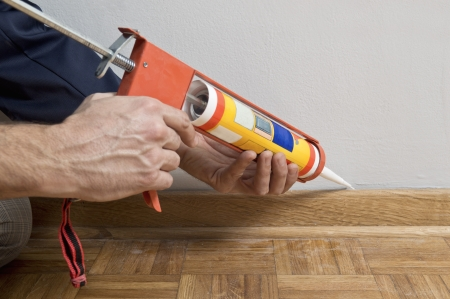 Caulking silicone from cartridge on wooden batten  photo