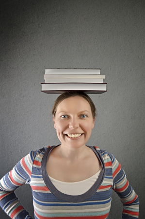 Smiling student with books on her head. photo