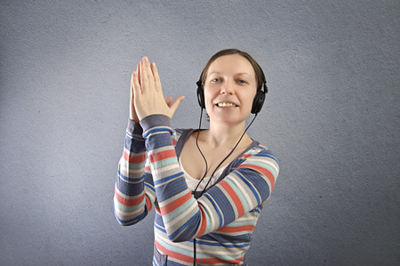 Portrait of a beautiful woman with headphones listening to music. Stock Photo