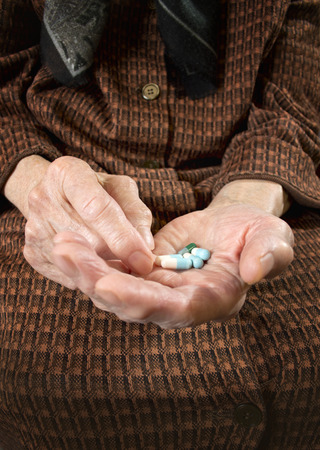 Senior woman holding assorted capsules in her hands conceptual of health care for the elderly.