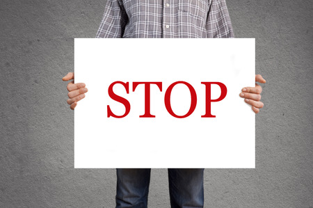 Person holding white banner with STOP message. Stock Photo