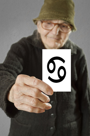 foretelling: Elderly woman holding card with printed horoscope Cancer sign. Selective focus on card and fingers.