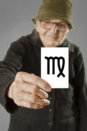 foretelling: Elderly woman holding card with printed horoscope Virgo sign. Selective focus on card and fingers.